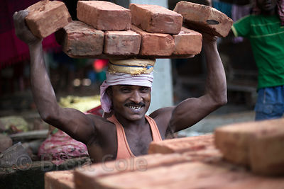 Construction laborers carry bricks on their heads in Salkia, Howrah, India. Much work in India is still done in a slow, round...