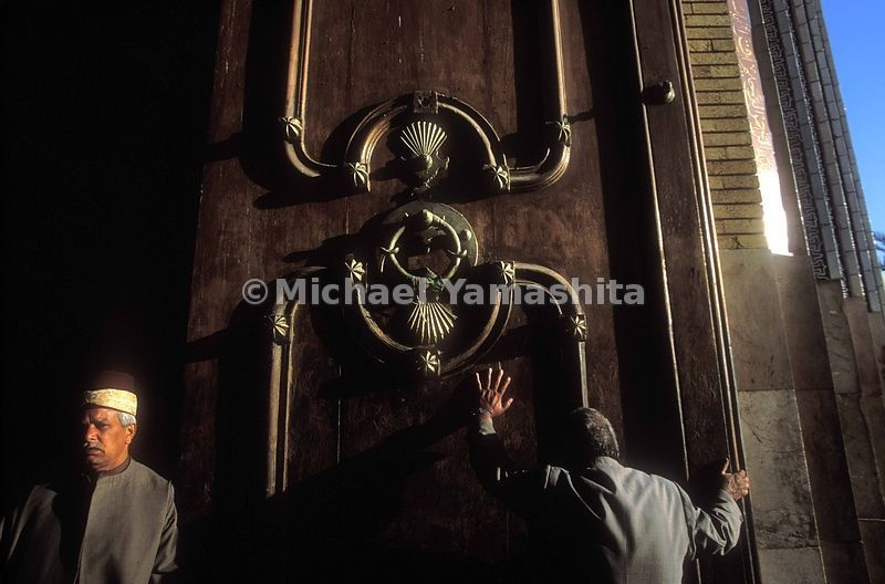 A devotee kisses the door of Khadiman Mosque.