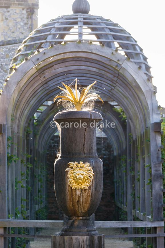 Carved oak urns with gilded lions' heads and agaves with domed pergola beyond in the Collector Earl's Garden designed by Julian and Isabel Bannerman. Arundel Castle Gardens, Arundel, West Sussex, UK