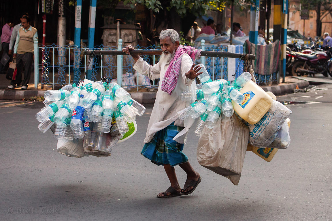 A man carries plastic for recycling through the street near Newmarket, Kolkata, India.