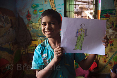 A boy hold up a drawing he made at the Child In Need Institute (CINI, cinindia.org) drop-in shelter at Sealdah Railway Statio...