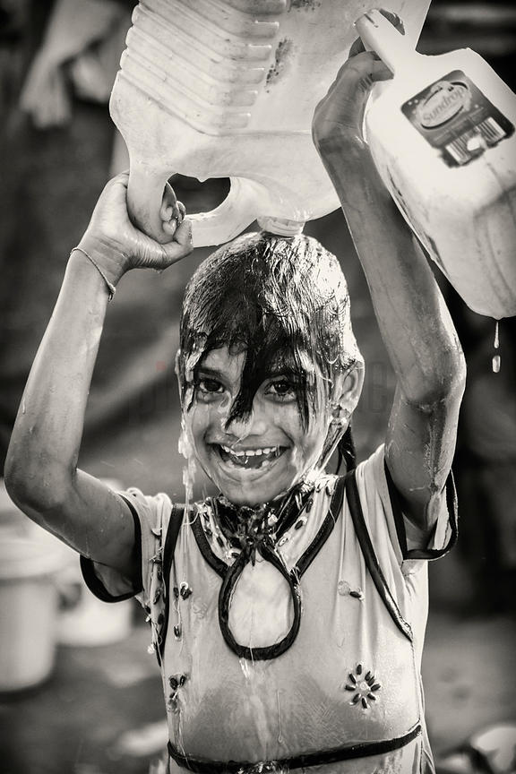 Young Child Pouring Water over her Head in New Delhi Slum