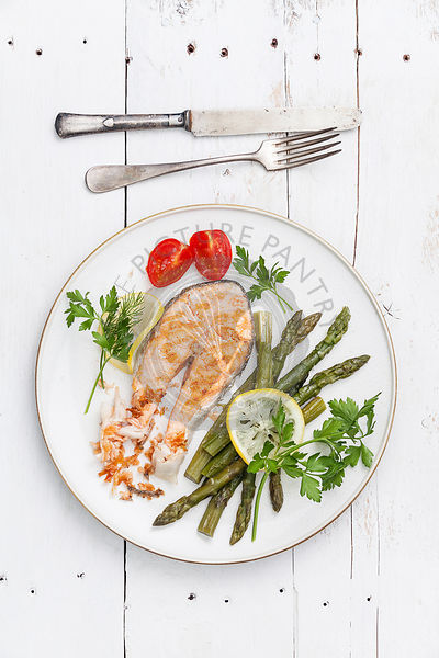 Grilled salmon with asparagus on white plate