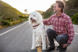 Large White Poodle Mix Dog Smiling Next to Man