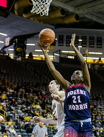 Robert Morris' Mikalah Mulrain (21) drives to the basket as Iowa's Bethany Doolittle (51) defends during the first half of pl...