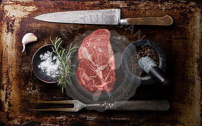 Raw fresh marbled meat Steak Rib eye Black Angus, seasoning and fork and knife on dark background