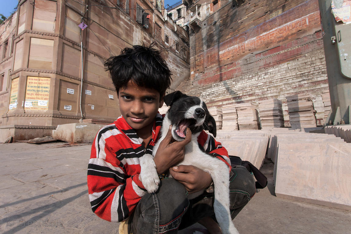 A boy plays with a stray puppy near Mir Ghat, Varanasi, India.