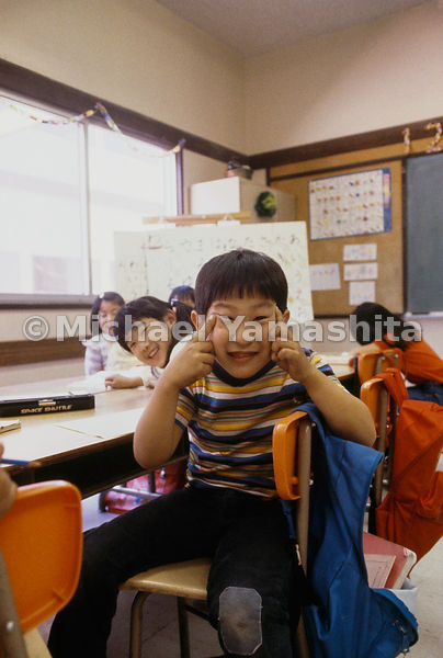 Class clown turns a gesture of ridicule into a good-natured acknowledgment of his heritage at a Buddhist school in Gardena, C...