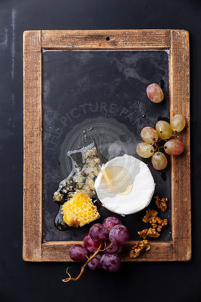 Cheese with honey, nuts and grapes on vintage slate chalk board