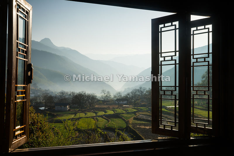 Windows at the Songtsam Tacheng lodge look out on terraced rice fields and misted peaks in Yunnan's northwest corner. The are...