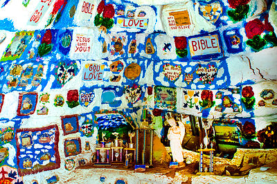 This is a small cave as part of the Salvation Mountain exhibit in California.