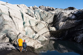 Tourists walking by the Sólhelmajökull glacier in Iceland.
