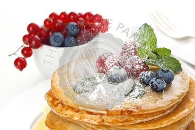 Small pancakes topped with honey, red currants and bilberries with Powdered sugar on white background