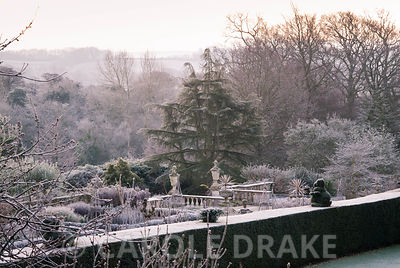 View from Temple Mount across the yew hedging bordering the croquet lawn to the formal terrace with balustrading and urns, tr...