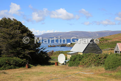 Part of Carcass Settlement with building, satellite dish, trees, landing stage and boat, Carcass Island, Falkland Islands