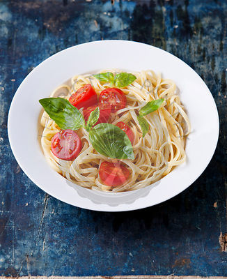Spaghetti with tomato and basil on blue wooden background