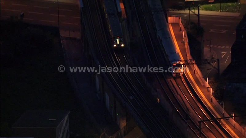 Aerial footage of trains passing through a station in London at night