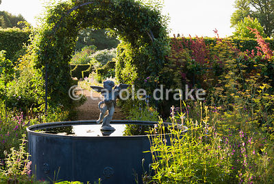 Lead fountain with putto and dolphin at the centre of the Organic Kitchen and Flower Garden, with apple tunnels shading the nearby paths. Arundel Castle Gardens, Arundel, West Sussex, UK