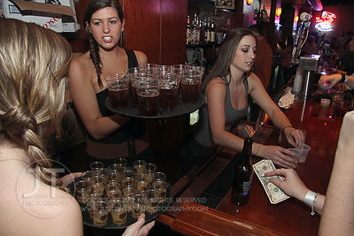 Bacardi promo girls and bartender Danielle Parker work at the Airliner Bar, 22 S Clinton Street in downtown Iowa City Saturda...
