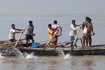 Workers row a boat full of sand down the Ganges River to a construction site in Kolkata, India.