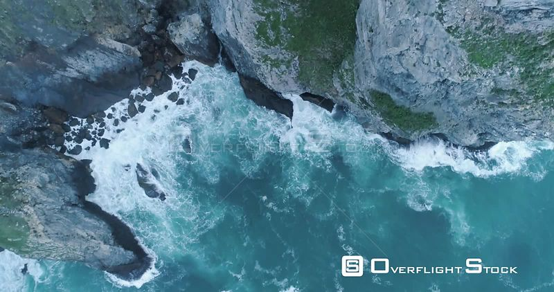 Aerial drone looking down at rocky cliffs and waves crashing off the beautiful coast of Portugal