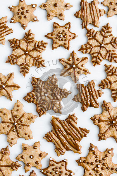 Decorated Snowflake cookies are photographed from the top view.
