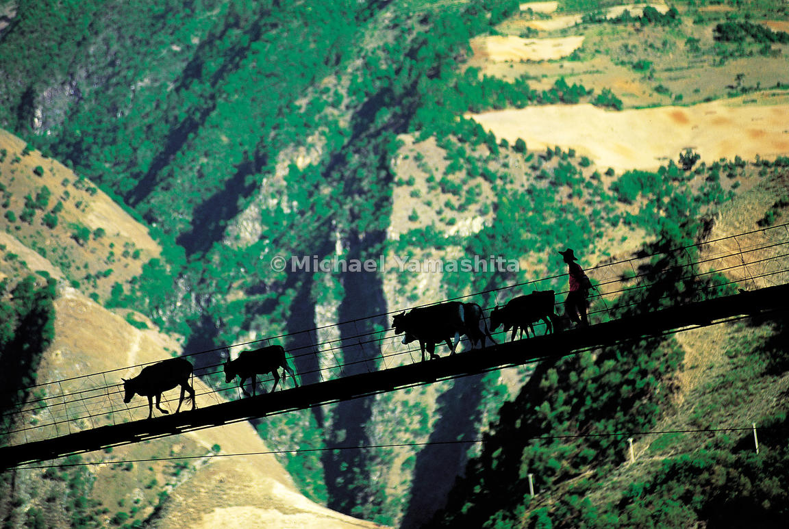 A Chinese farmer returning home from the market crosses a narrow rope suspension bridge strung across a ravine. The Mekong Ri...