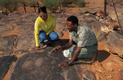 Ancient San rock engravings, Nama guide shows a visitor, Riemvasmaak, Northern Cape, South Africa