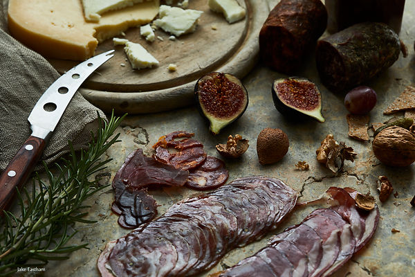 charcuterie, cured meats, salami, ham, grapes, cheese, crackers, wine, bread, nuts, figs