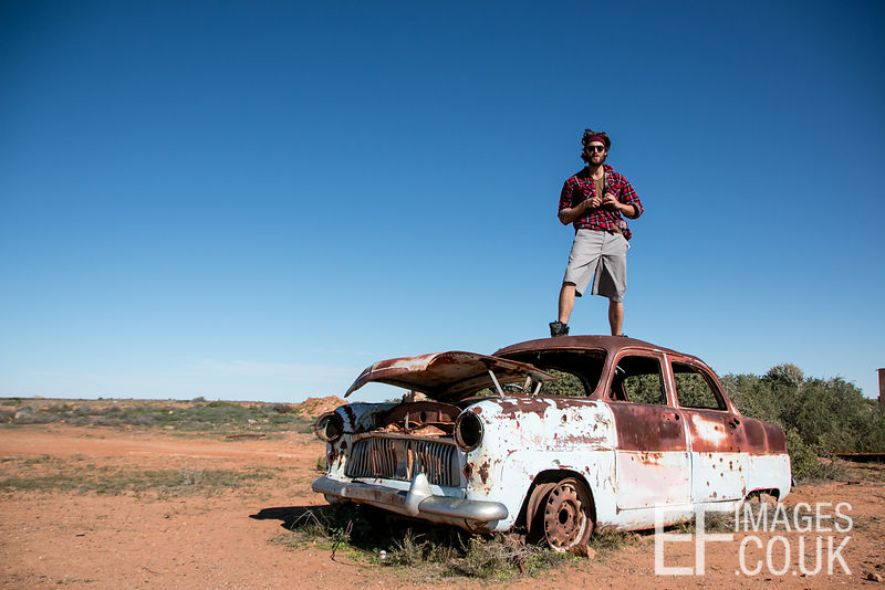 Man Standing On Rusted Up Old Car In The Outback