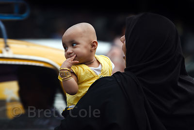 A Muslim woman holds a baby girl in yellow, near Crawford Market, Mumbai, India.
