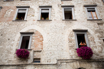Italy - Gubbio - a woman leans out of a window in a mediaevel building