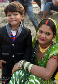 A mother and son during Chhath Puja, Varanasi, India. Chhath Puja is a devotion to the Sun God Surya in which people gather a...