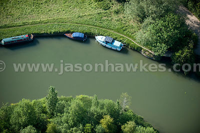 Aerial view of boats moored to banks of river