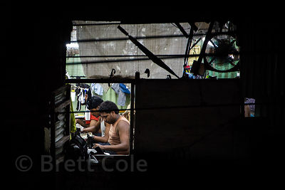 Men work in a garment factory in a slum area in Bandra East, Mumbai, India.