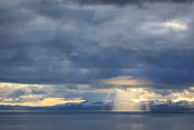 A ray of light breaks through the cloud over the Isle of Skye as sunset approaches in the Scottish Highlands.