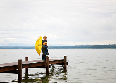 Children with yellow umbrella on dock