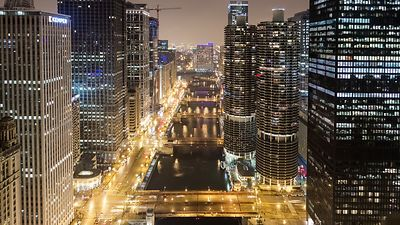 Bird's Eye: Wide Shot of an Iconic View Down Chicago River's Four Bridges & Marina Towers Lit Up During Rush Hour