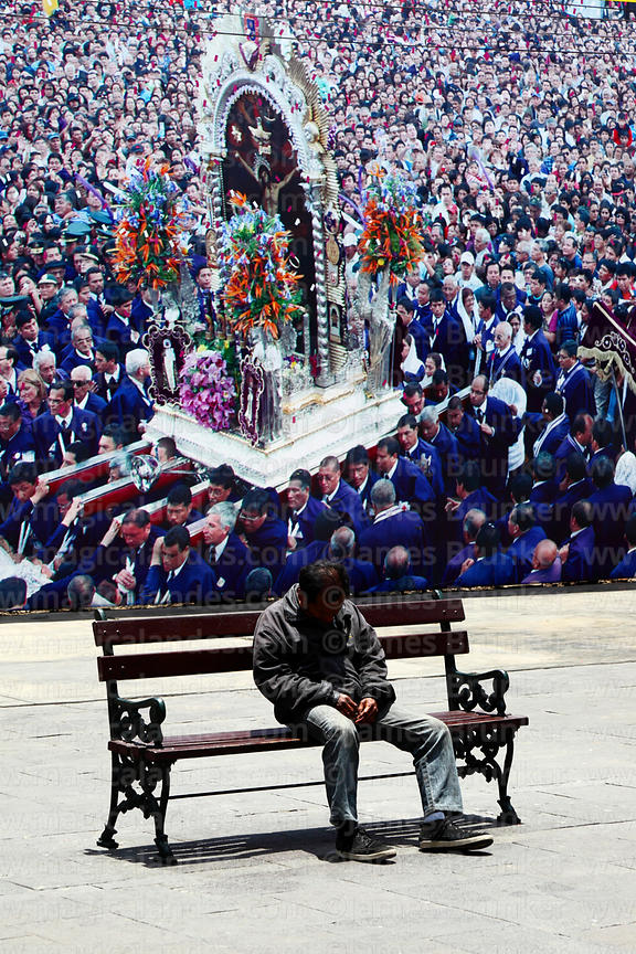 Man sleeping on bench in front of photographic mural of Señor de los Milagros parades, Lima, Peru