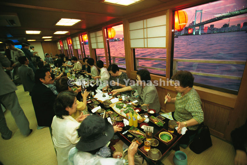 Aboard a yakatabune, a sight-seeing dinner boat, where diners indulge traditional tastes with ample sake. In the distance is ...