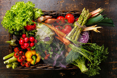 Fresh vegetables in basket on wooden background