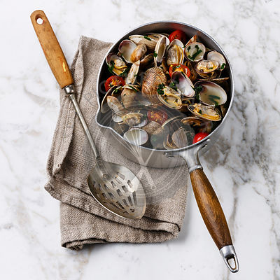 Vongole Shells Clams with tomato and parsley in cooking pan on white marble background