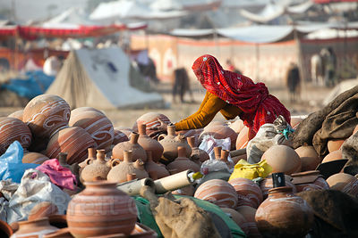 A woman tends to a stall selling clay pots at the Pushkar Camel Mela, Pushkar, India.