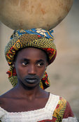 Peul girl, with characteristic mouth tattoo carrying water, Djenné, Mali