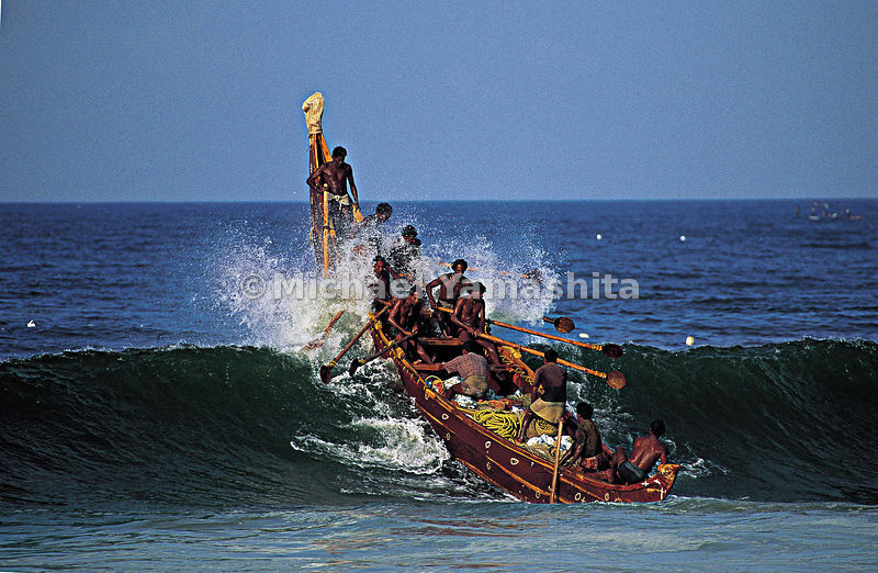 Boat full of men rides atop of a wave in India.