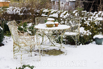 Wire work table and chairs on snowy terrace surrounded by shrubs and seedheads of perennials. Yews Farm, Martock, Somerset, UK