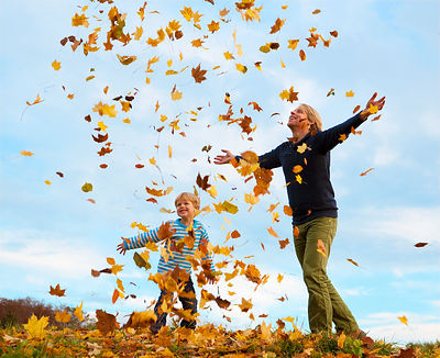 father and son Throwing Autumn Leaves into the Air