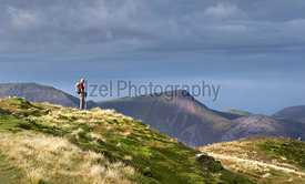 LAKE DISTRICT, CUMBRIA, ENGLAND, UK - OCTOBER 08, 2016: An elderly hiker taking in the views from the summit of Dale Head in ...