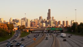 Wide Shot: Busy Evening Commute On The Kennedy Expressway Facing Chicago's Skyline (Sunset)