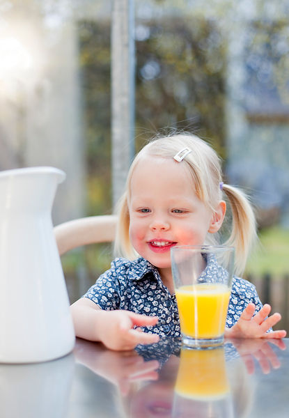 Toddler girl with glass of juice